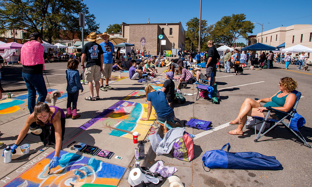 . Artists and attendees work and mingle along East Fifth Street in downtown Loveland Saturdy morning Sept. 10, 2016 during Pastels On 5th, a free to enter and attend sidewalk chalk art festival now in its sixth year. Pastels was designed as a benefit for Alternatives to Violence, a group committed to the intervention in, education about, and prevention of domestic violence, sexual assault, and other violent crimes. (Photo by Michael Brian/Loveland Reporter-Herald)