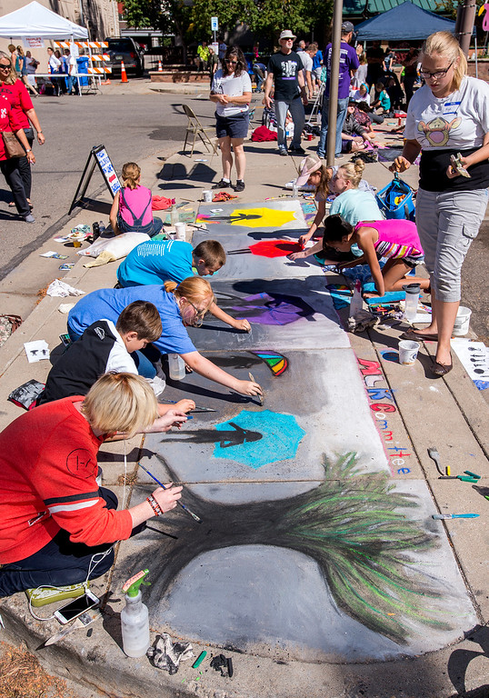 . Thompson School District students work on a Loveland Integrated School of the Arts group project involving K-12 students selected from the entire district Saturday morning Sept. 10, 2106 during the Pastels On 5th sidewalk chalk art festival in downtown Loveland. (Photo by Michael Brian/Loveland Reporter-Herald)