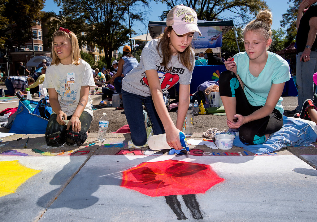 . Thompson School District students Cordelia Bowlus, left, Annalina Scalise, center, and Lauren Alexander, right, work on a Loveland Integrated School of the Arts group project involving K-12 students selected from the entire district Saturday morning Sept. 10, 2106 during the Pastels On 5th sidewalk chalk art festival in downtown Loveland. (Photo by Michael Brian/Loveland Reporter-Herald)