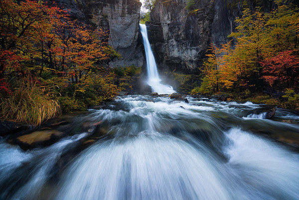 A beautiful waterfall lined with fall colors in Patagonia, Argentina