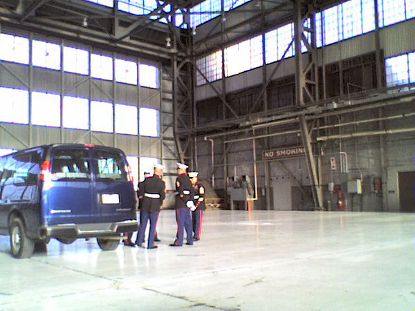 The Marine honor guard waiting in  a base hanger for Maria's jet to arrive.