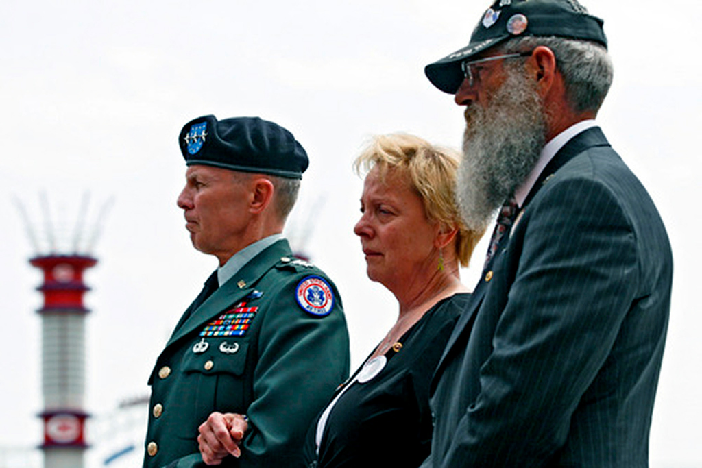 LTG James Campbell, retired (CQ), representing the U.S. Army escorts Carolyn and Keith Maupin (CQ), as they watch the casket of their son Matt be put into the hurst during a celebration service Sunday.  Staff photo by Nick Graham