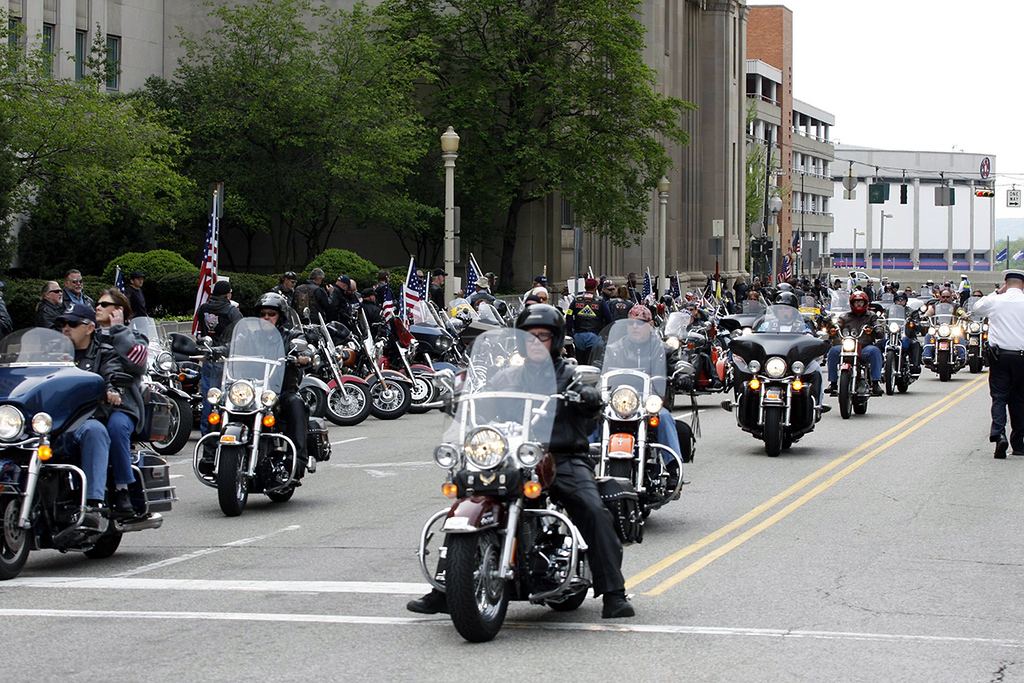 The procession winds through the Cincinnati streets as riders parked along the curbs fall in line.