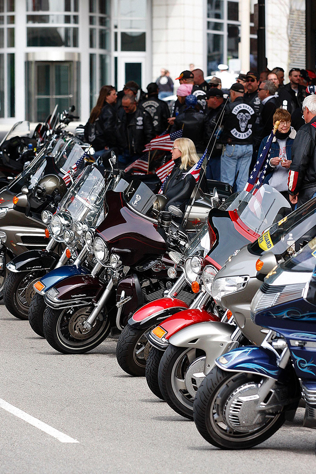 Members of many different motorcycle groups wait to join the procession outside of the ball park