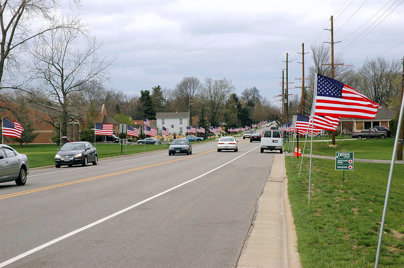 The Springboro Optimist Club, with the help of about 30 volunteers, rounded up about 300 large American flags and lined South Main Street and the funeral procession route.