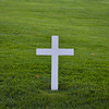 White Christian Cross surrounded by green grass