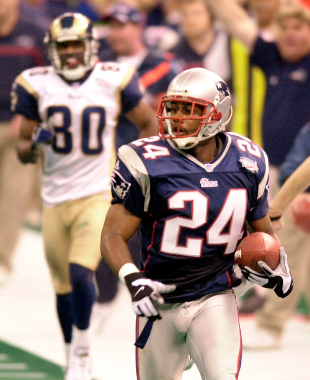 . New England Patriots cornerback Ty Law (24) is trailed by St. Louis Rams\' Isaac Bruce (80)  as he scores a touchdown during second-quarter play of Super Bowl XXXVI at the  Louisiana Superdome Sunday, Feb. 3, 2002 in New Orleans.  (AP Photo/Tony Gutierrez)