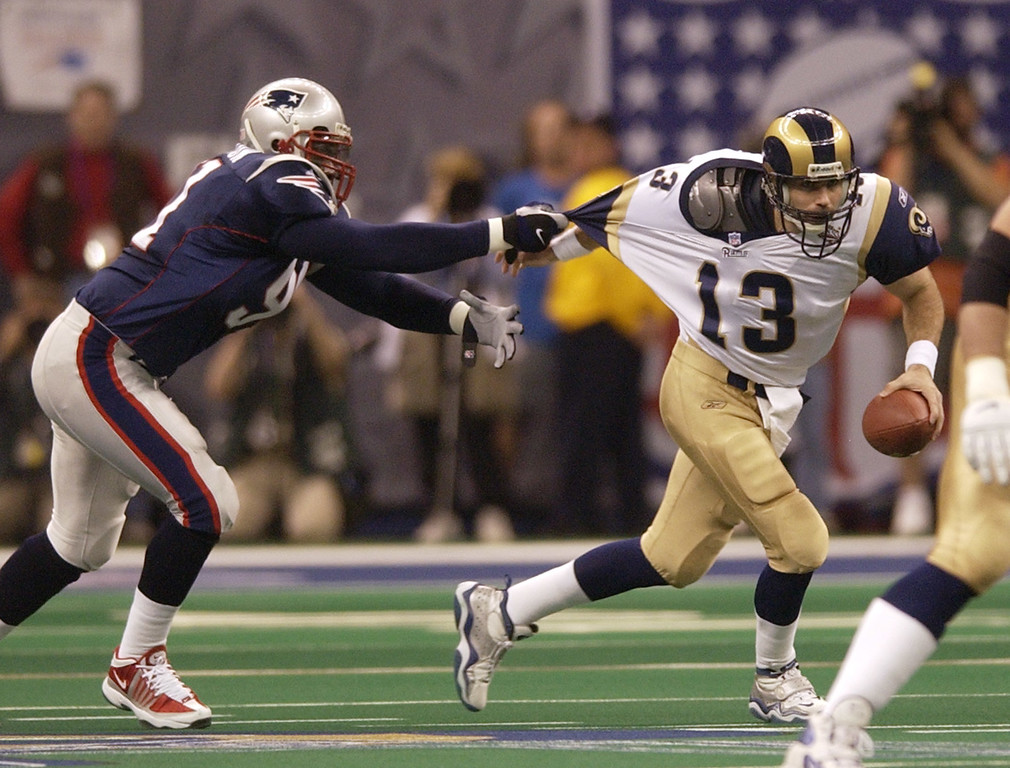 . New England Patriots\' Bobby Hamilton (91) sacks St. Louis Rams quarterback Kurt Warner (13) near the end of the first quarter of Super Bowl XXXVI Sunday, Feb. 3, 2002, in New Orleans. (AP Photo/David J. Phillip)