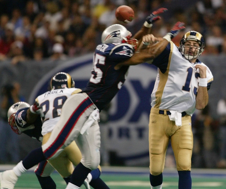 . St. Louis Rams quarterback Kurt Warner, left, throws the ball as New England Patriots\' Roman Phifer (95) defends during the third quarter of Super Bowl XXXVI at the Louisiana Superdome, Sunday, Feb. 3, 2002  in New Orleans. The pass was blocked and fell incomplete. Blocking on the play is Rams\' Marshall Faulk (28). (AP Photo/Doug Mills)