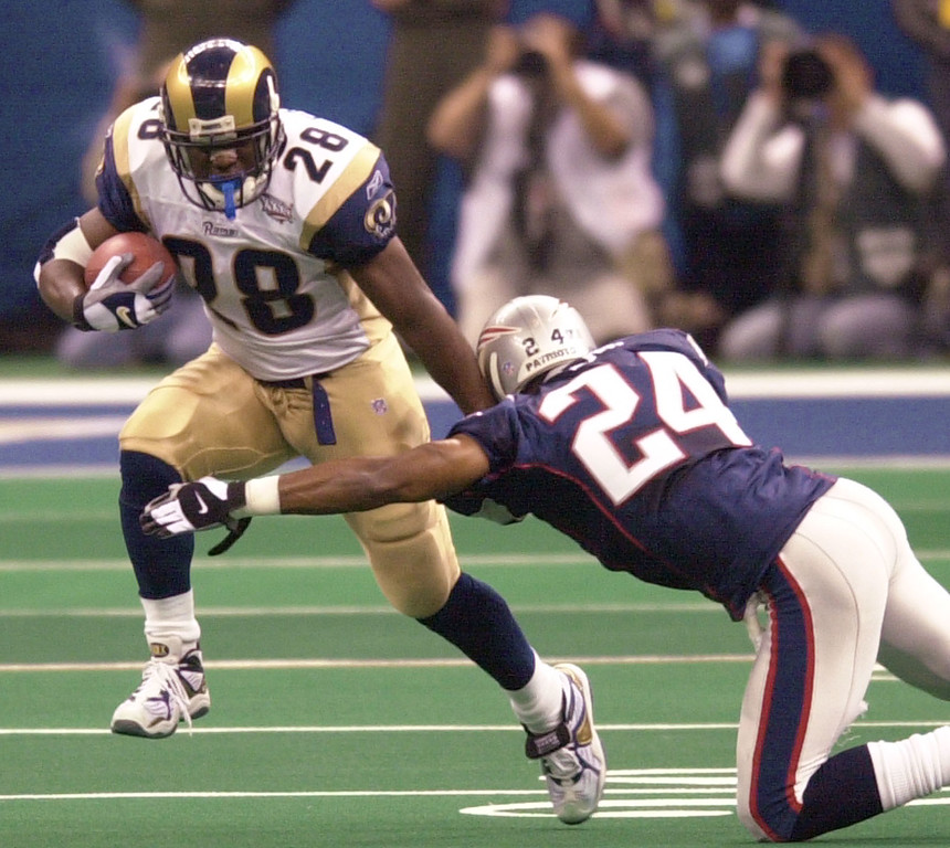 . St. Louis Rams running back Marshall Faulk (28) fends of New England Patriots cornerback Ty Law (24) during first-quarter play of Super Bowl XXXVI at the  Louisiana Superdome Sunday, Feb. 3, 2002 in New Orleans.  (AP Photo/Tony Gutierrez)