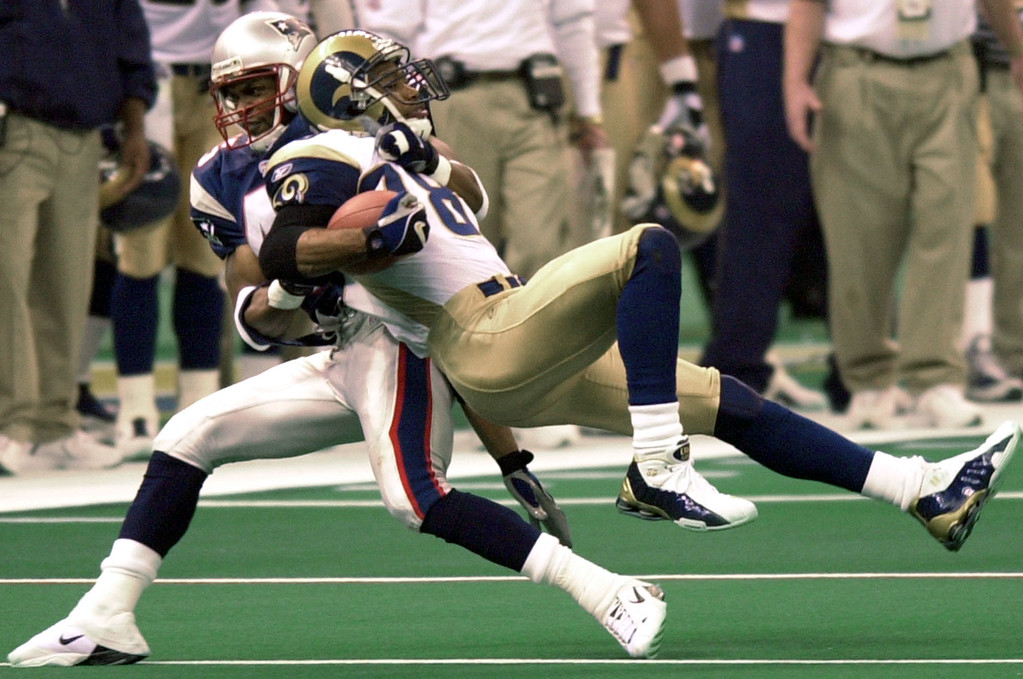 . New England Patriots cornerback Otis Smith (45) takes down St. Louis Rams wide receiver Torry Holt (88) during third-quarter play of Super Bowl XXXVI at the  Louisiana Superdome Sunday, Feb. 3, 2002 in New Orleans.  (AP Photo/Tony Gutierrez)