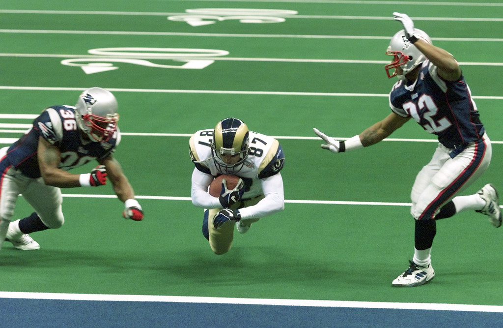 . St. Louis Rams\' Ricky Proehl dives between New England Patriots defenders Lawyer Milloy (36) and Terrance Shaw (22) into the end zone to tie the score for the Rams late in the fourth quarter of Super Bowl XXXVI, Sunday, Feb. 3, 2002, in New Orleans. (AP Photo/Rick Bowmer)