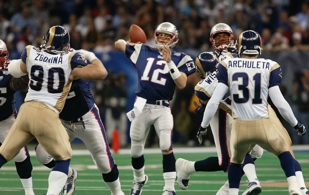 . New England Patriots quarterback Tom Brady (12) throws as St. Louis Rams\' Jeff Zgonina (90) and Adam Archuleta (31) defend during the third quarter of Super Bowl XXXVI at the Louisiana Superdome, Sunday, Feb. 3, 2002, in New Orleans. (AP Photo/Doug Mills)
