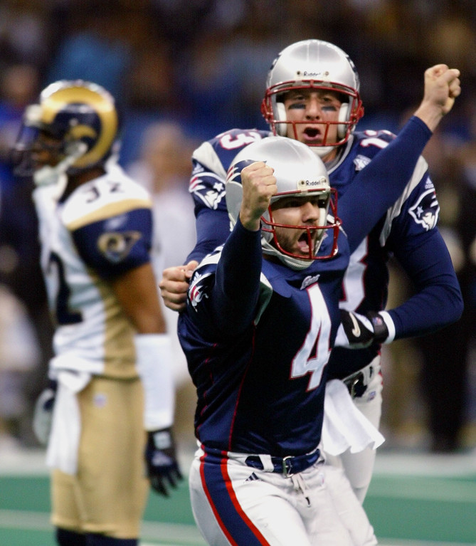 . New England Patriots\' kicker Adam Vinatieri (4) celebrates with teammate Ken Walter, back, after kicking a game-winning 48-yard field goal to beat the St. Louis Rams 20-17  in Super Bowl XXXVI at the Louisiana Superdome, Sunday, Feb. 3, 2002, in New Orleans. Rams\' Dre\' Bly is at left. (AP Photo/Doug Mills)