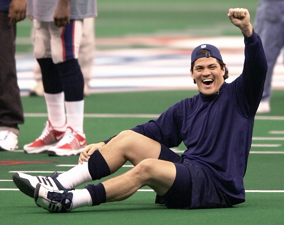 . New England Patriots linebacker Tedy Bruschi reacts to fans who were yelling his name from the stands during warmups for Super Bowl XXXVI at the Louisiana Superdome, Sunday, Feb. 3, 2002, in New Orleans. (AP Photo/Tony Gutierrez )