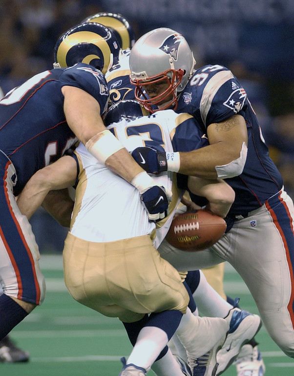 . St. Louis Rams quarterback Kurt Warner is sacked in the third quarter by New England Patriots defenders Mike Vrabel, left, and Richard Seymour (93) in Super Bowl XXXVI at the Louisiana Superdome, Sunday, Feb. 3, 2002, in New Orleans. (AP Photo/Amy Sancetta)