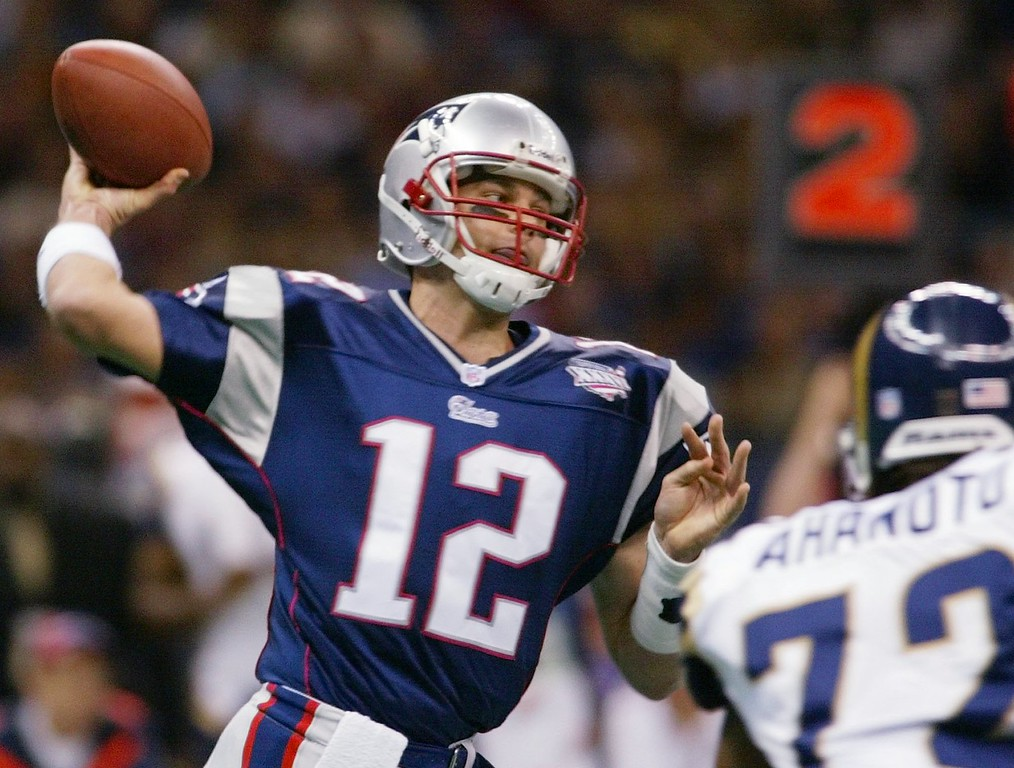 . New England Patriots quarterback Tom Brady passes under pressure by St. Louis Rams\' Chidi Ahanotu (72) in the first quarter against the New England Patriots in Super Bowl XXXVI at the Louisiana Superdome, Sunday, Feb. 3, 2002 in New Orleans. (AP Photo/Doug Mills)