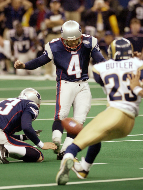 . New England Patriots kicker Adam Vinatieri (4) boots a 48-yard field goal out of the hold of Ken Walter (13) to win Super Bowl XXXVI 20-17 over the St. Louis Rams Sunday, Feb. 3, 2002, in New Orleans. (AP Photo/David J. Phillip)