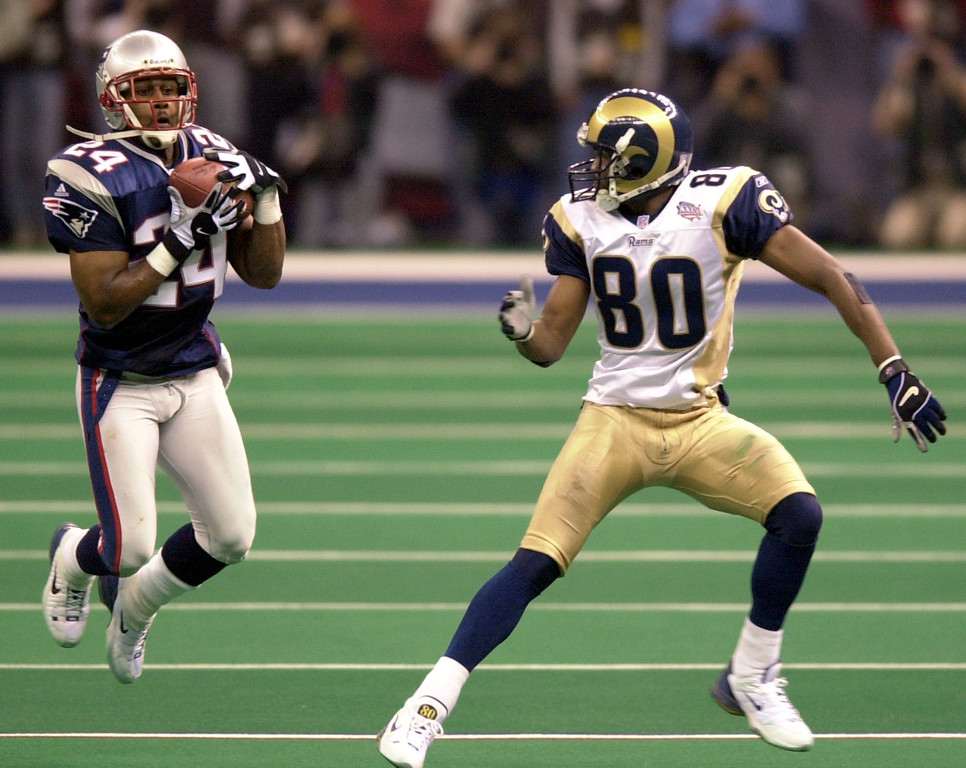 . New England Patriots cornerback Ty Law (24) intercepts a pass from St. Louis Rams quarterback Kurt Warner as intended receiver Isaac Bruce (80) looks on during Super Bowl XXXVI, Sunday, Feb. 3, 2002, in New Orleans. Law returned the interception for a touchdown. (AP Photo/Tony Gutierrez)