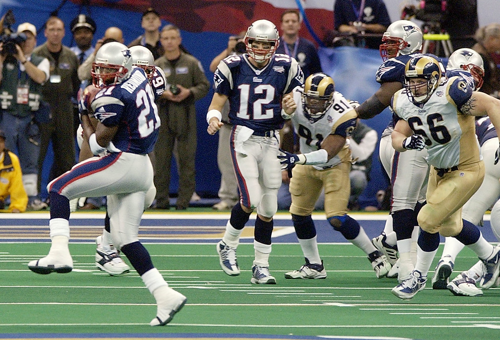 . New England Patriots\' J.R. Redmond (21) pulls down a pass from Tom Brady (12) during the final drive against the St. Louis Rams during Super Bowl XXXVI, Sunday, Feb. 3, 2002, in New Orleans. The completion helped set up the winning 48-yard field goal by Adam Vinatieri with no time left. (AP Photo/Kathy Willens)