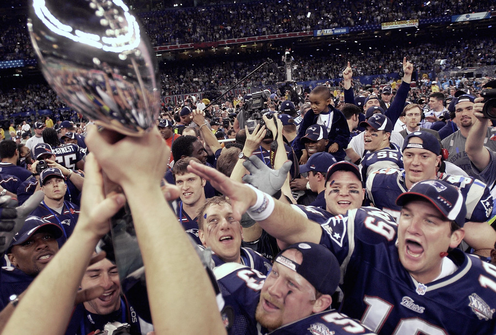 . New England Patriots players reach out to touch the Vince Lombardi Trophy after they beat the St. Louis Rams 20-17 to win Super Bowl XXXVI Sunday, Feb. 3, 2002, in New Orleans. (AP Photo/David J. Phillip)