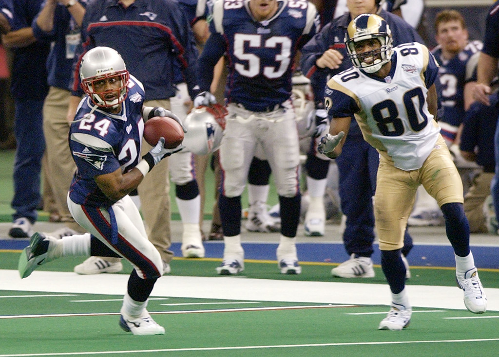 . New England Patriots cornerback Ty Law (24) intercepts a pass from St. Louis Rams quarterback Kurt Warner as intended receiver Isaac Bruce (80) looks on during Super Bowl XXXVI, Sunday, Feb. 3, 2002, in New Orleans. (AP Photo/Kathy Willens)