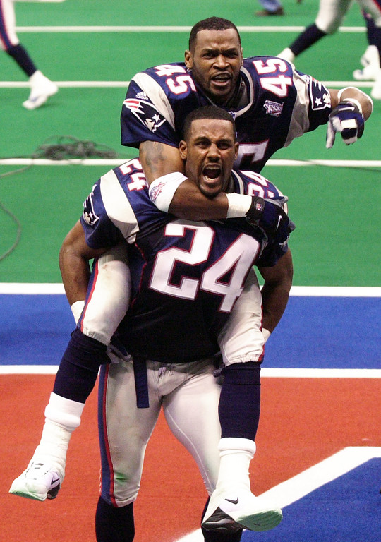 . New England Patriots cornerback Otis Smith (45) celebrates on the back of teammate cornerback Ty Law (24) after the Patriots beat the St. Louis Rams in Super Bowl XXXVI at the  Louisiana Superdome Sunday, Feb. 3, 2002 in New Orleans.  (AP Photo/Tony Gutierrez)