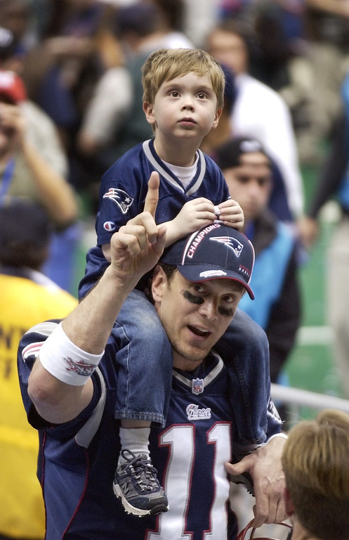 . New England Patriots quarterback Drew Bledsoe with his son, Stuart, on his shoulders, gives the number one sign after the Patriots defeated the Rams 20-17 in the final seconds of Super Bowl XXXVI, Sunday, Feb. 3, 2002, in New Orleans. (AP Photo/Kathy Willens)