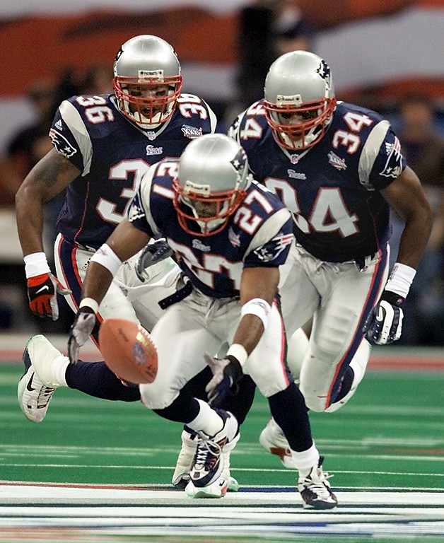 . New England Patriots\' cornerback Terrell Buckley (27) scoops up a St. Louis Rams fumble in front of Patriots\' Lawyer Milloy (36) and Tebucky Jones (34) in Super Bowl XXXVI  Sunday, Feb. 3, 2002, in New Orleans. (AP Photo/Michael Conroy)