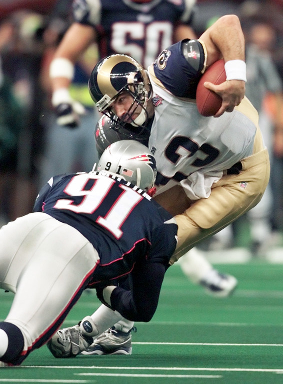 . New England Patriots\' Bobby Hamilton (91) sacks St. Louis Rams quarterback Kurt Warner (13) near the end of the first quarter of Super Bowl XXXVI Sunday, Feb. 3, 2002, in New Orleans. (AP Photo/Michael Conroy)