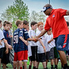 Former Patriots player, Derrick Beasley high-fives a group of kids at the Patriots Football Clinic for kids. SUN/Caley McGuane