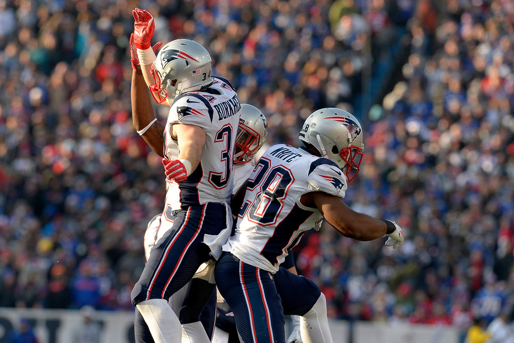 . New England Patriots running back Rex Burkhead, left, celebrates his touchdown run with James White (28) and others during the second half of an NFL football game against the Buffalo Bills, Sunday, Dec. 3, 2017, in Orchard Park, N.Y. (AP Photo/Adrian Kraus)