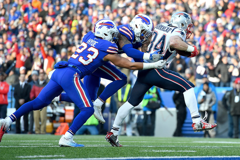 . New England Patriots running back Rex Burkhead, right, fights his way into the end zone for a touchdown as Buffalo Bills free safety Jordan Poyer (21) and strong safety Micah Hyde (23) try to stop him during the second half of an NFL football game, Sunday, Dec. 3, 2017, in Orchard Park, N.Y.(AP Photo/Rich Barnes)