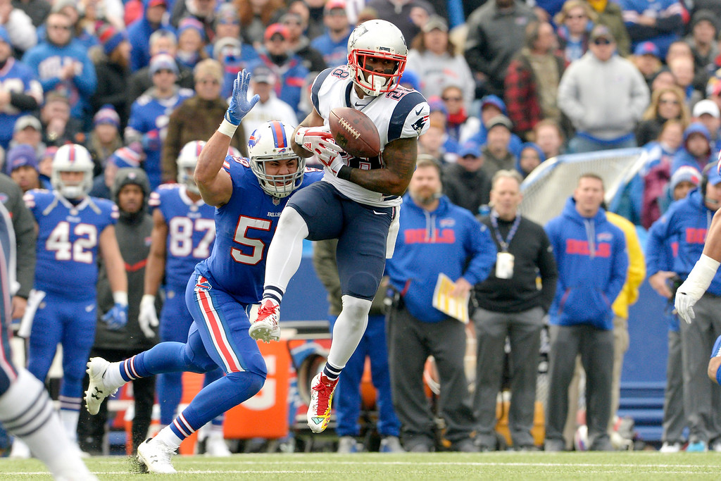 . New England Patriots running back James White, right, tries to make a catch as Buffalo Bills outside linebacker Matt Milano (58) defends during the first half of an NFL football game, Sunday, Dec. 3, 2017, in Orchard Park, N.Y. (AP Photo/Adrian Kraus)