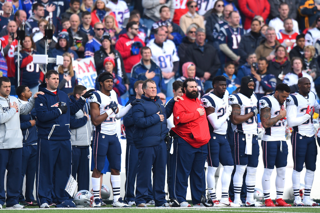 . New England Patriots head coach Bill Belichick, center, and his team listen to the national anthem prior to an NFL football game against the Buffalo Bills, Sunday, Dec. 3, 2017, in Orchard Park, N.Y. (AP Photo/Rich Barnes)