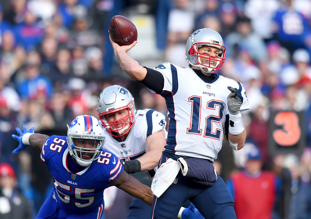 . New England Patriots quarterback Tom Brady (12) throws a pass as Buffalo Bills defensive end Jerry Hughes (55) rushes by the block of offensive tackle Nate Solder (77) during the first half of an NFL football game, Sunday, Dec. 3, 2017, in Orchard Park, N.Y. (AP Photo/Rich Barnes)