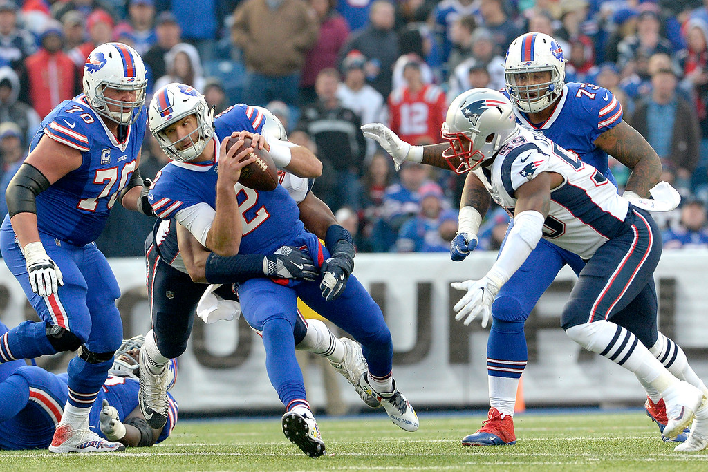 . Buffalo Bills quarterback Nathan Peterman (2) scrambles as New England Patriots defensive tackle Deatrich Wise, back, grabs at him for a tackle during the second half of an NFL football game, Sunday, Dec. 3, 2017, in Orchard Park, N.Y. (AP Photo/Adrian Kraus)