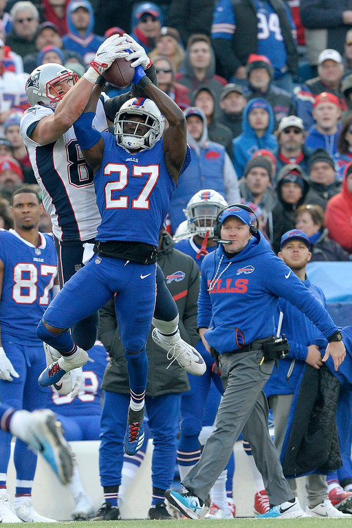 . New England Patriots tight end Rob Gronkowski, left, makes a catch as Buffalo Bills cornerback Tre\'Davious White (27) defends during the second half of an NFL football game, Sunday, Dec. 3, 2017, in Orchard Park, N.Y. Bills head coach Sean McDermott, right, looks on during the play. (AP Photo/Adrian Kraus)