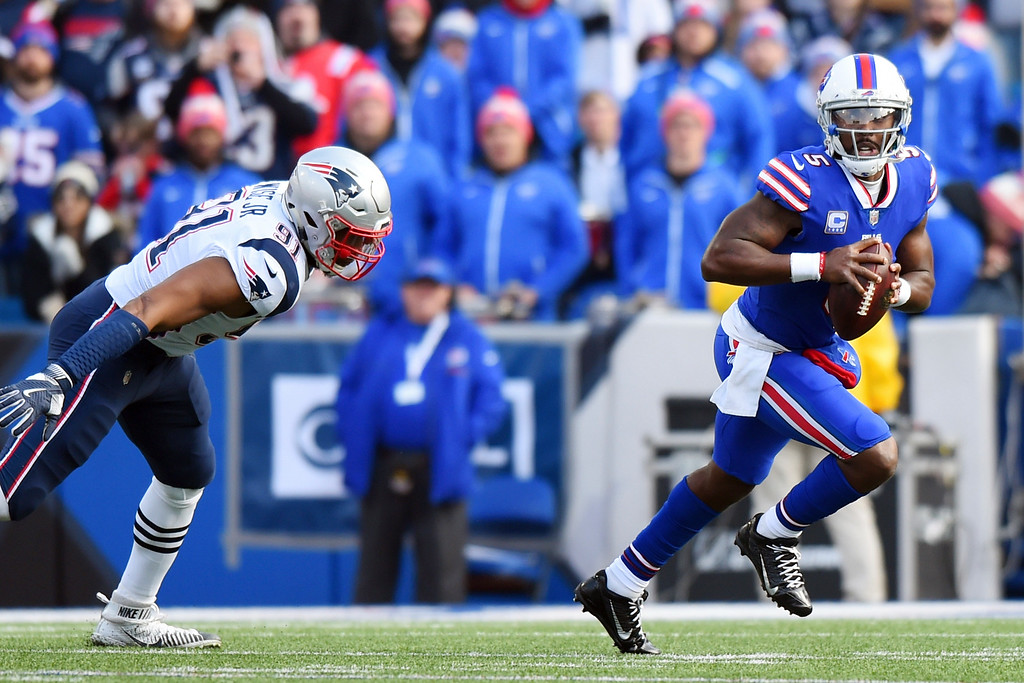 . Buffalo Bills quarterback Tyrod Taylor, right, scrambles as New England Patriots defensive tackle Deatrich Wise (91) chases after him during the first half of an NFL football game, Sunday, Dec. 3, 2017, in Orchard Park, N.Y. (AP Photo/Rich Barnes)