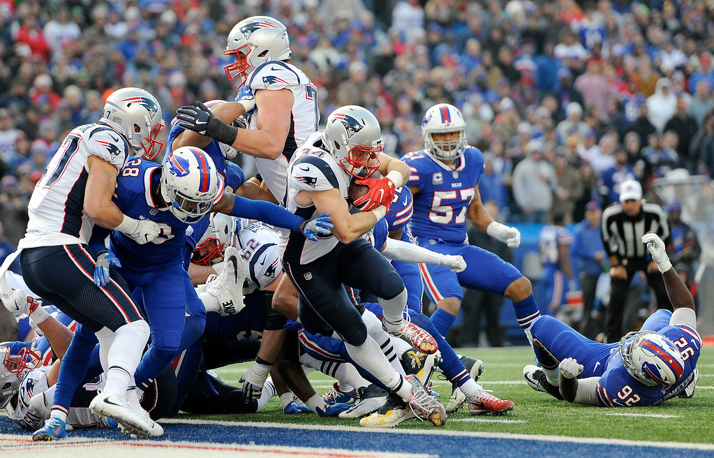 . New England Patriots running back Rex Burkhead, center, rushes in for a touchdown against the Buffalo Bills during the second half of an NFL football game, Sunday, Dec. 3, 2017, in Orchard Park, N.Y. (AP Photo/Adrian Kraus)