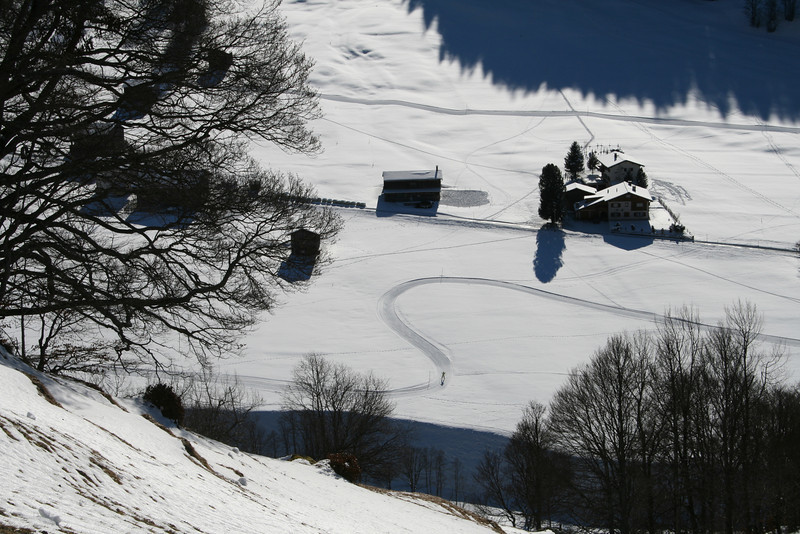A lone cross-country skier makes a graceful loop in a distant valley; Switzerland.
