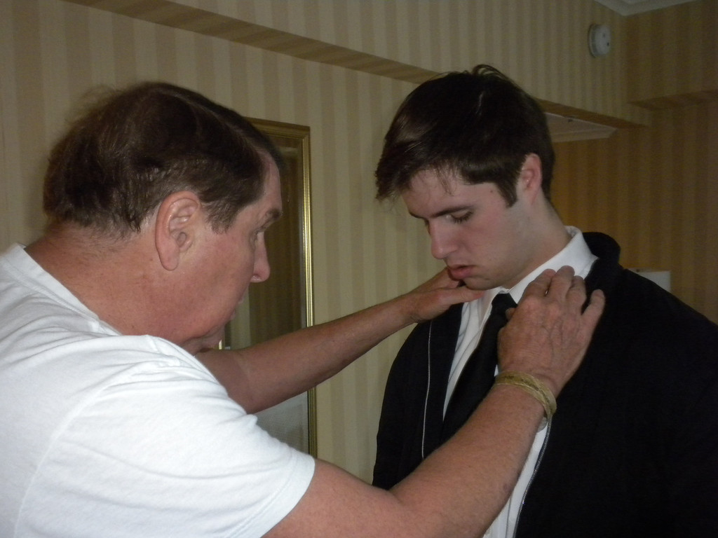 Tom helping Paul arrange his shirt and tie to put the final touches on his appearance before Paul's performance at Carnegie