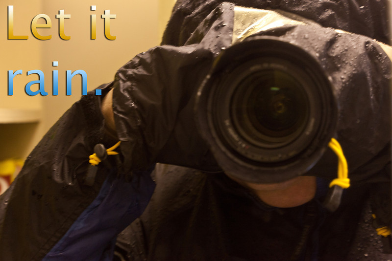 Paul in mirror with camera. Camera covered with rain shield. Saying Let it rain.