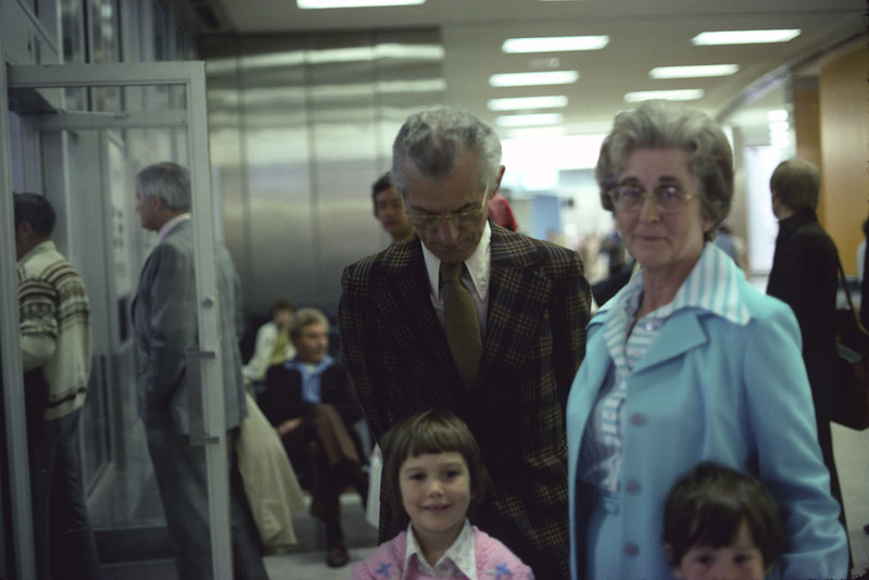 Lloyd and Jean Lantz waiting at Toronto Airport in 1976 with grandchildren Kate and Joanne. Scanned from slide 2008 May 19th. Politician John Turner behind door at left.