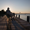 Nicholas Perry reads a book on the shore of Chautauqua Lake as the sun sets on Wednesday, June 14, 2017. PAULA OSPINA / STAFF PHOTOGRAPHER