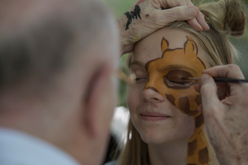John Scott Williams, face paints a giraffe on Izzie Coan, 16,  on Sunday, July 2, 2017 on Clark road. PAULA OSPINA / STAFF PHOTOGRAPHER
