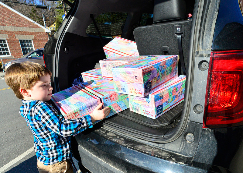 KKRISTOPHER RADDER — BRATTLEBORO REFORMER<br /> Ryker Bauer, 5, of Hinsdale, N.H., pulls out 12 boxes at the Hinsdale Post Office that he mails to various humane societies  on Wednesday, March 4, 2020. Bauer has mailed 112 packages as part of a project he created called Pawsome Box.