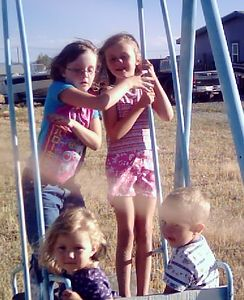 Michaela, Heather, Leah and Justin, on Michaela's swing, Aug. 9, 2004