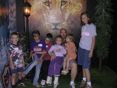 Jason and all the kids sitting on the bench by the Lamp Post, with Aslan in the background