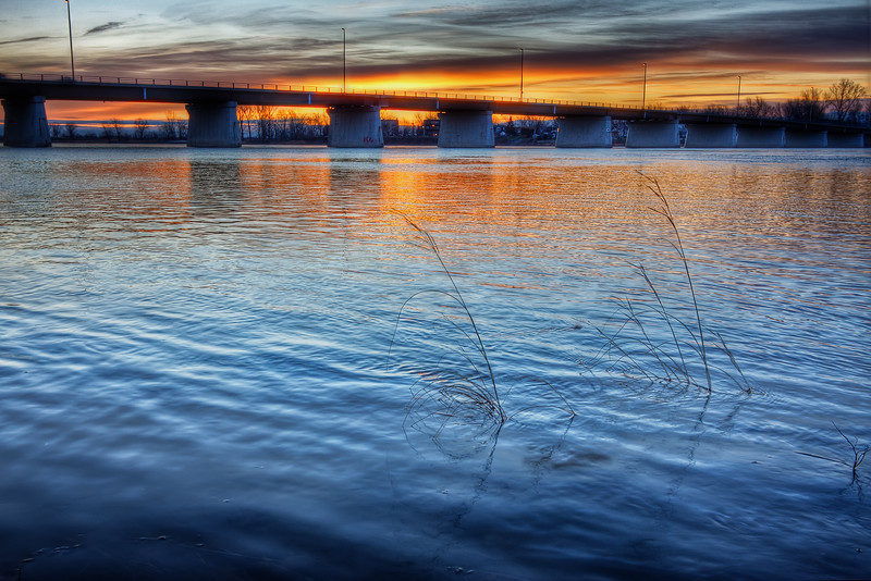 Sunrise from river with bridge.